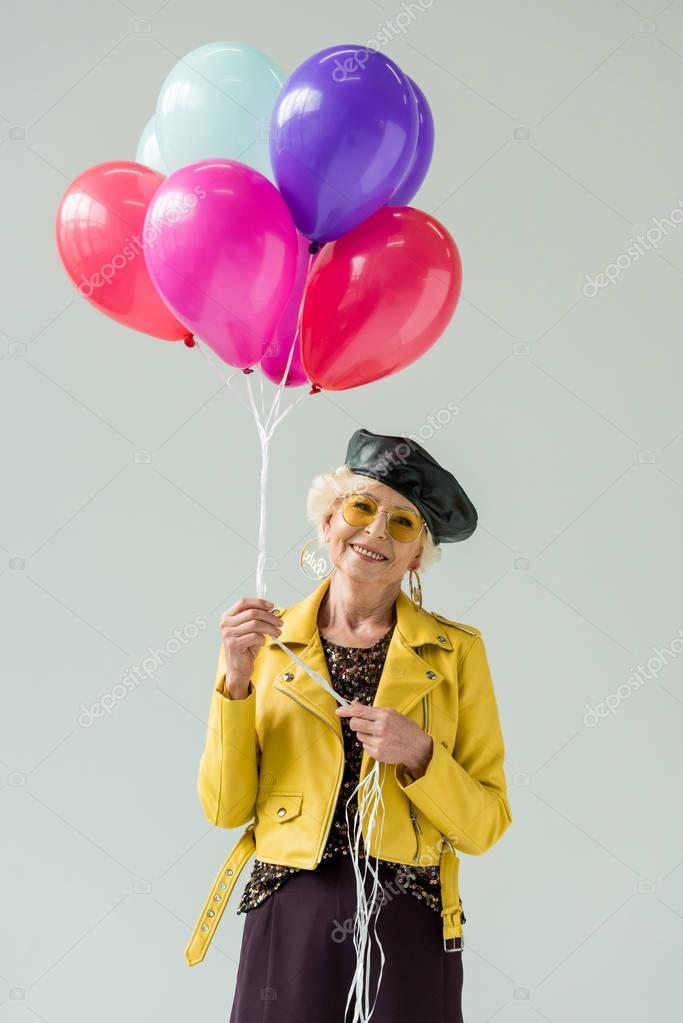 stylish senior woman with colorful balloons