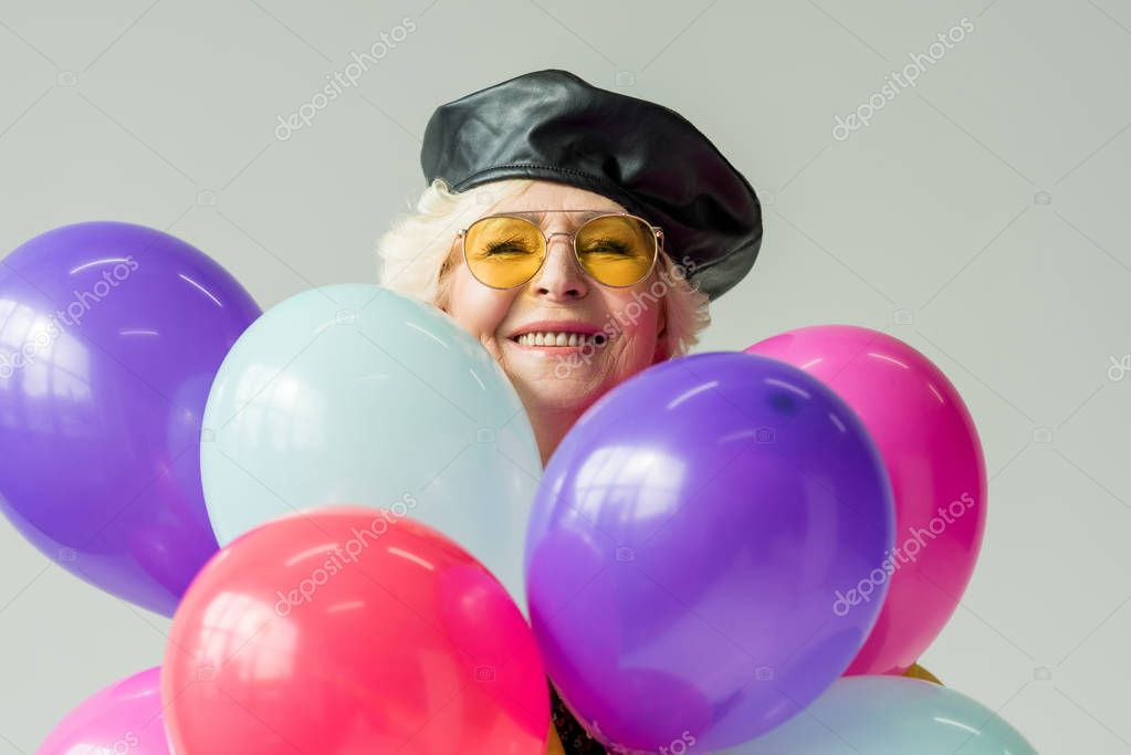 senior woman with colorful balloons
