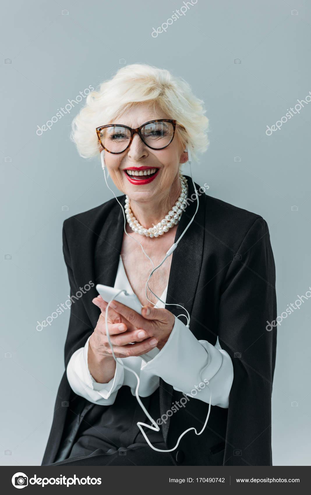 Mosolyogva vezető hölgy gyöngy nyaklánc hallgat zenét a fülhallgató és a  smartphone 74fdf46806