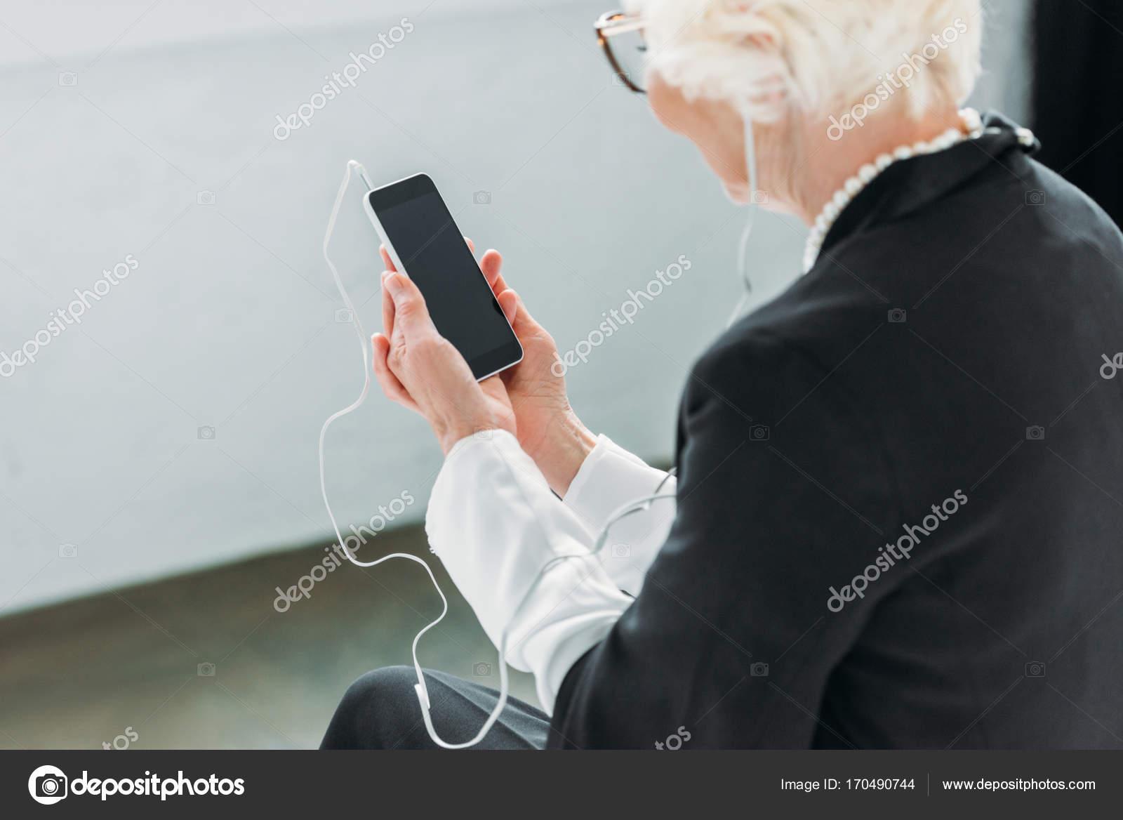 Hátulnézet a vezető hölgy gyöngy nyaklánc hallgat zenét a fülhallgató és  smartphone — Fotó szerzőtől AllaSerebrina d7da148e71