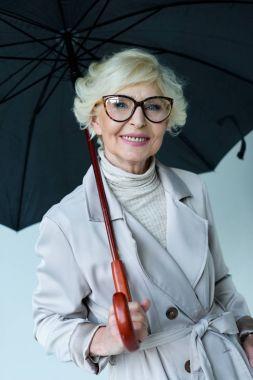 senior lady in trench coat with umbrella
