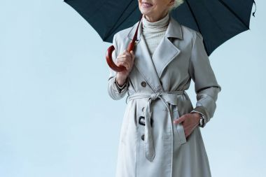 lady in trench coat holding umbrella
