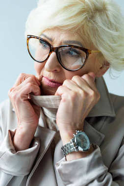 senior lady in trench coat and eyeglasses
