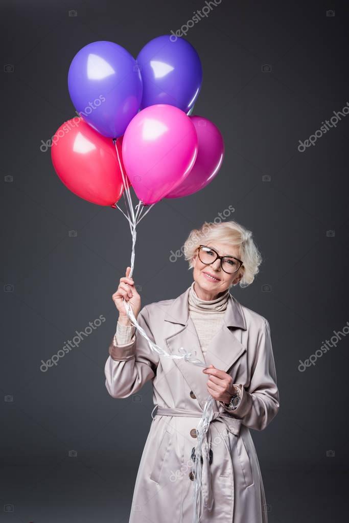 senior lady holding balloons