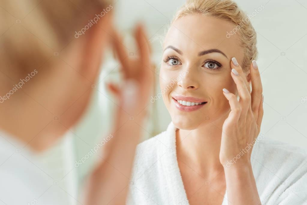 beautiful woman looking at mirror