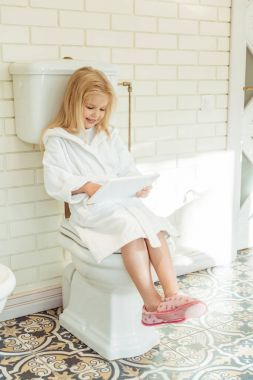 child with digital tablet on toilet