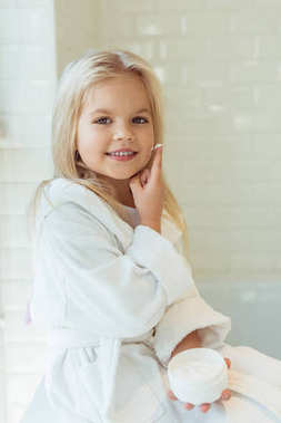 child in bathrobe applying face cream