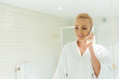 woman in bathrobe talking on smartphone