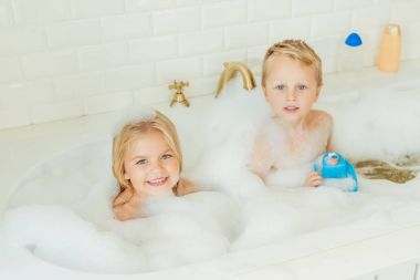 kids playing in bathtub with foam