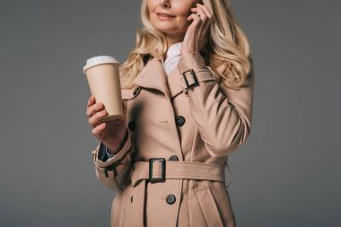 woman in trench coat talking by phone