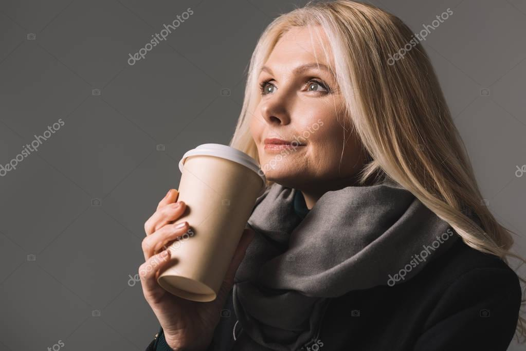 mature woman with coffee to go
