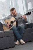 Fotografia suonare la chitarra acustica uomo