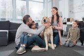 Family sitting on floor with dog