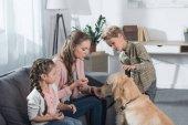 Mutter und Kinder spielen mit Hund