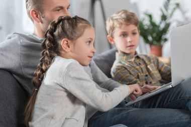 Father sitting with children and laptop