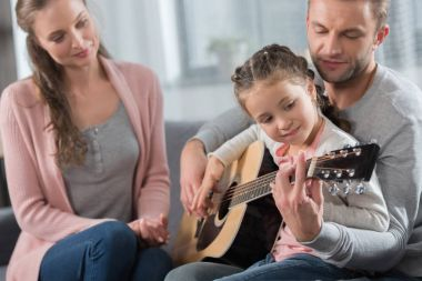 Father teaching daughter guitar