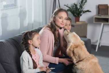 Mother sitting with children and dog
