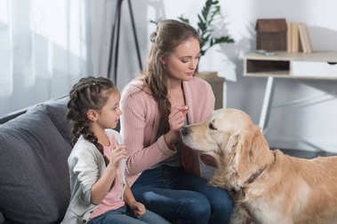 mother and daughter petting dog