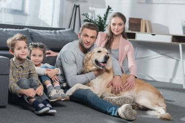 Family and dog sitting on floor