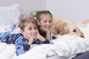 kids on bed with dog