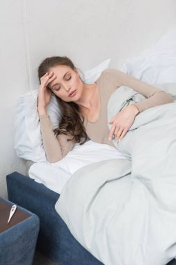 woman lying in bed with fever