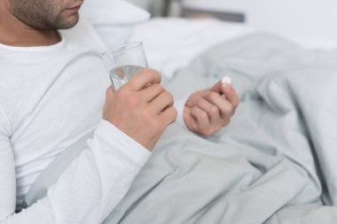 Sick man holding pill and glass