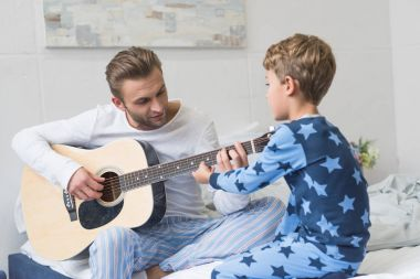 father showing son how play guitar