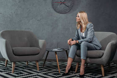 businesswoman sitting on armchair in waiting room