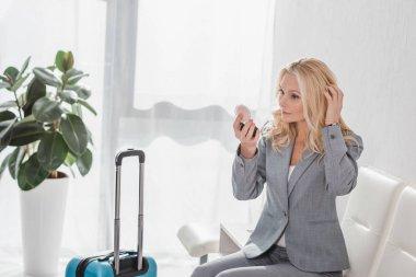 businesswoman doing makeup before trip