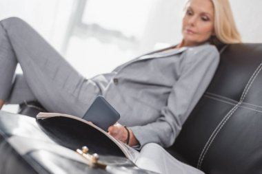 businesswoman using smartphone on couch