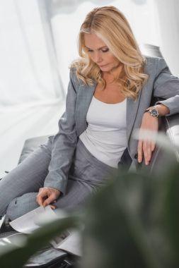 mature businesswoman reading magazine