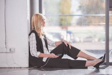 businesswoman sitting on floor and charging phone