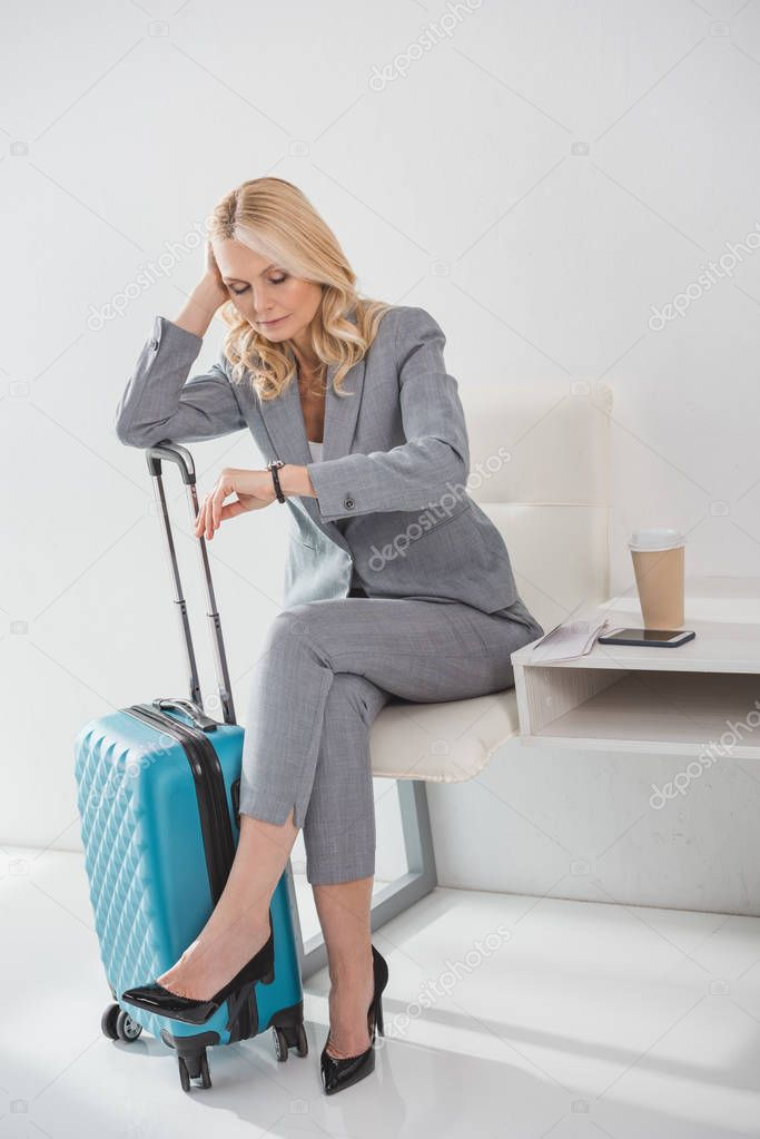 Tired mature businesswoman looking at watch while waiting for trip