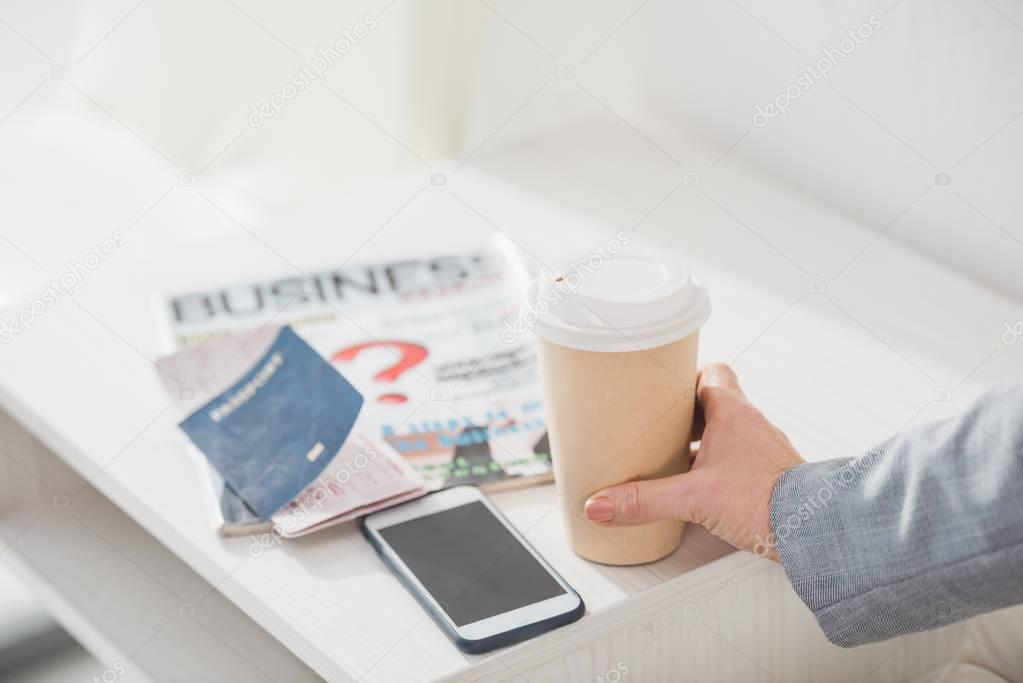 businesswoman holding paper cup of coffee