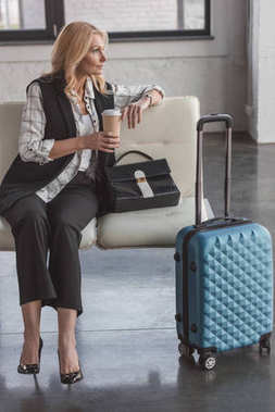 Beautiful middle aged woman with suitcase and coffee waiting for flight stock vector