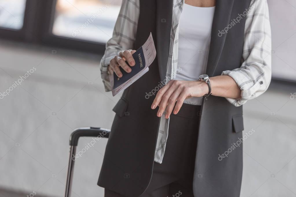 woman with flight ticket looking at watch