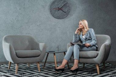 businesswoman sitting in armchair