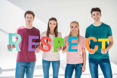 Happy young friends holding colorful word respect and smiling at camera on grey stock vector