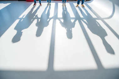 Cropped shot of young people standing together and shadows on grey stock vector