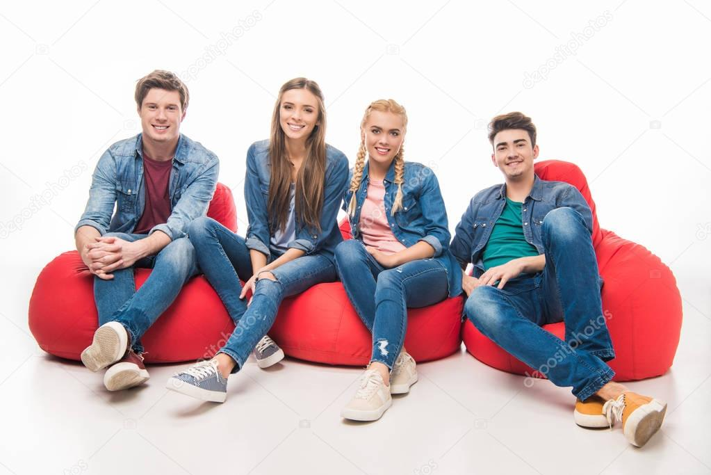 Cheerful young friends sitting on bean bag chairs and smiling at camera isolated on white stock vector