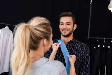 Beautiful happy young couple choosing necktie in boutique stock vector