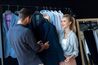 couple choosing suit in boutique
