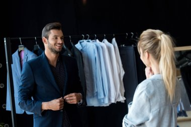 couple choosing suit in boutique