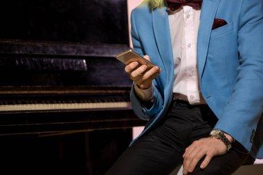 man using smartphone at piano