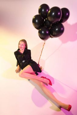 woman with black balloons