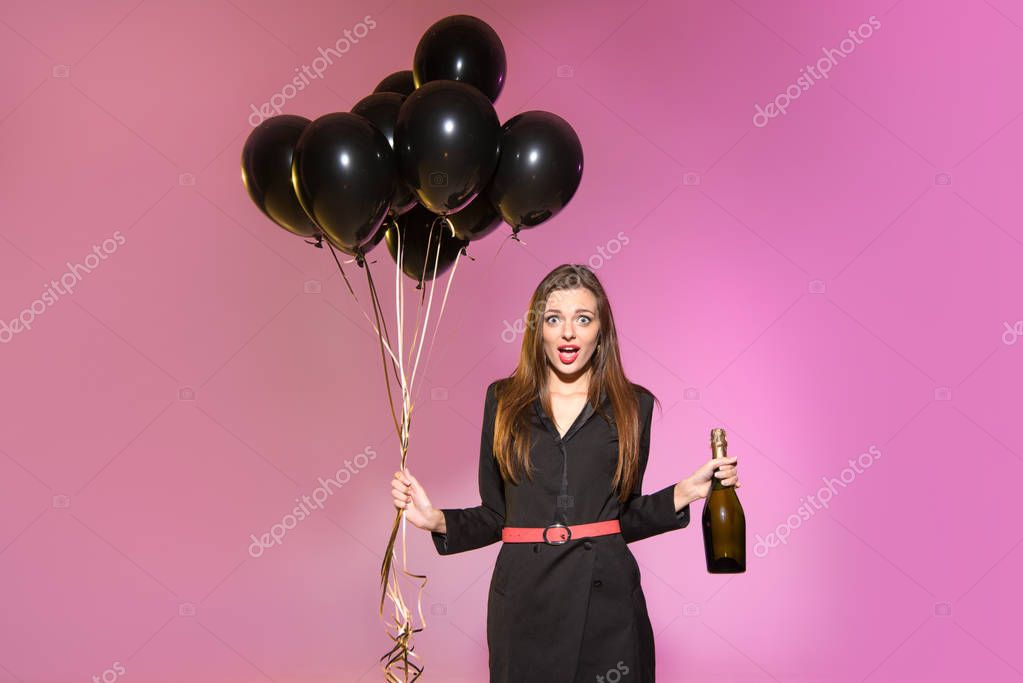 woman with champagne bottle and black balloons