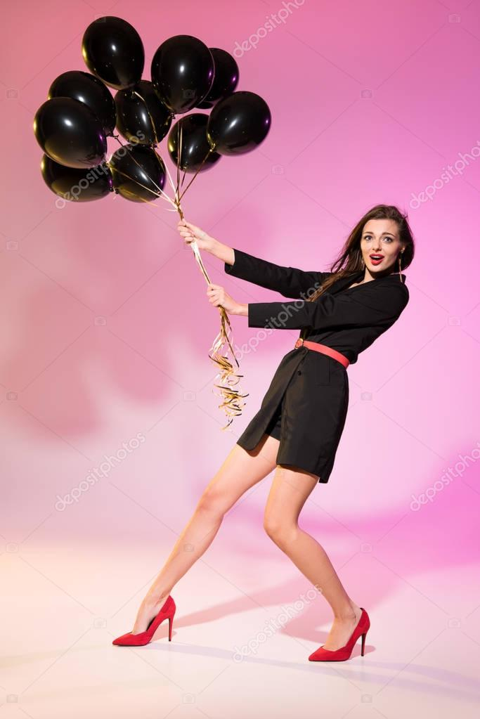 woman holding black balloons