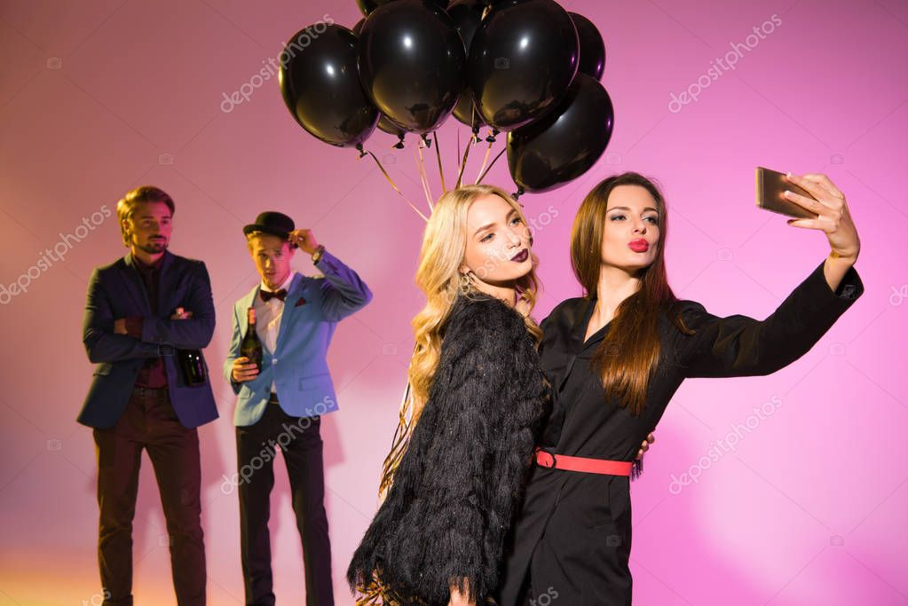 girls with balloons taking selfie
