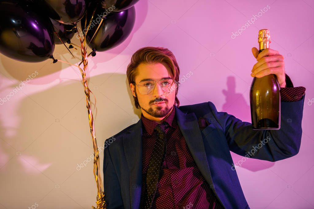 man with champagne and balloons