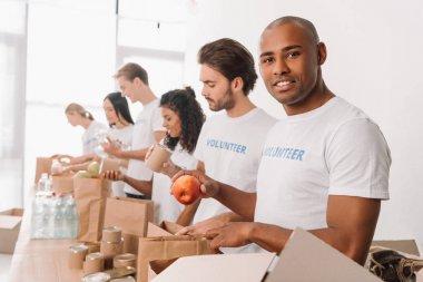 volunteer packing food into bag